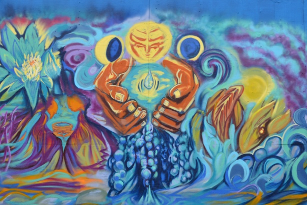 mural of large brown hands holding water