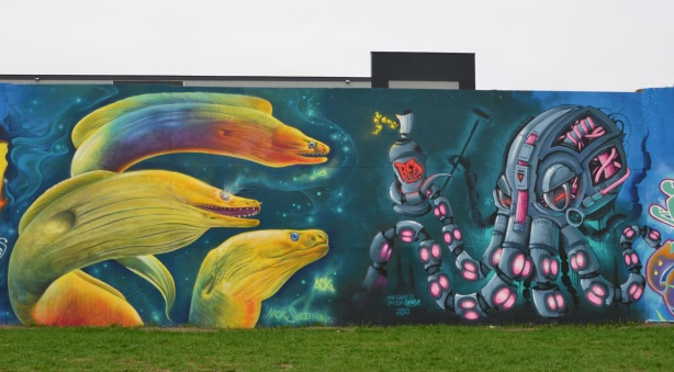 two murals. one is 3 large eel heads in yellos by Nick Sweetman, the other is a mechanical looking octopus