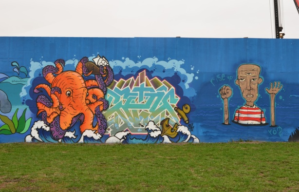 two murals on hoardings around new water treatment plant by Ashbridges, an orange octopus and a man in a red and white striped T shirt with words rise up