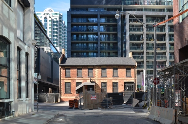 old red brick building being preserved in downtown Toronto, with newer taller buildings surrounding it