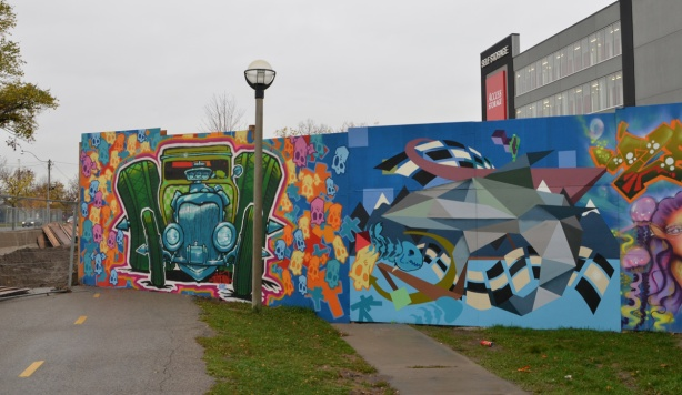 wallnoize street art murals on blue hoardings around new water treatment plant, one end of the hoardings, by the bike trail, an old green car by spud, and a graphic in neutral tones,