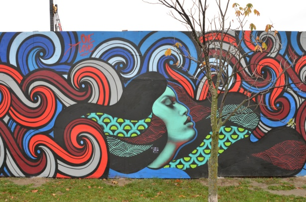wallnoize street art murals on blue hoardings around new water treatment plant, a woman with long flowing hair and with her eyes closed