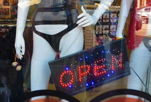 open sign in red and blue lights in the window of an adult store, beside white mannequin with very small black bikini bottoms and mesh top