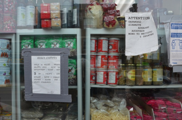 the window of a Greek grocery store, with food, also signs re covid rules in Greek. for sale, oregano, Nescafe coffee, tomato paste,