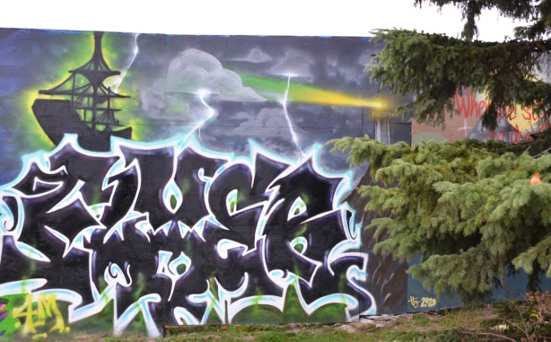 black and white wildstyle mural on blue hoardings, pine tree beside