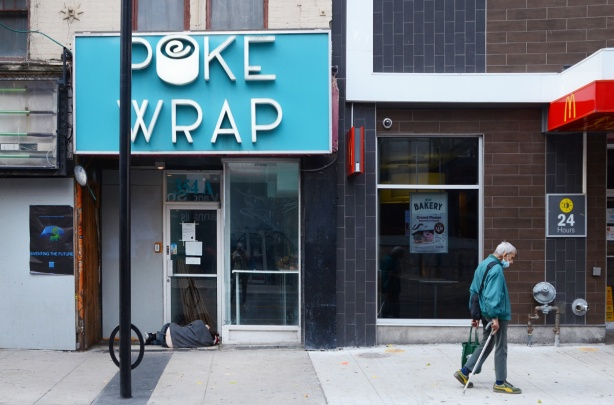 an old man walks up Yonge street past empty shops and a man sleeping in a doorway