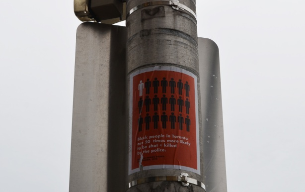 a poster on a metal utility pole with a graphi to illustrate how black people are more likely to be shot and or killed by the Toronto police
