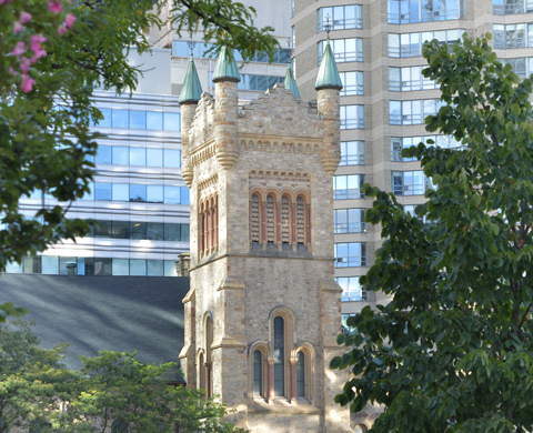 steeple of St. Andrews Presbyterian church with trees in the foreground and condos in the background . Corner of Simcoe and King streets