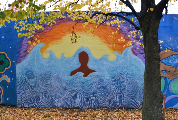 mural on hoardings near Ashbridge Bay water treatment facility, brown profile in water near yellow and orange shore