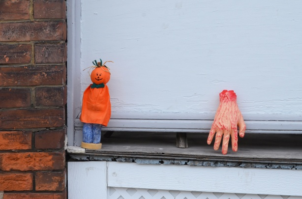 an an exterior window sill, a bloody h and, not real, and a small figure with a pumpkin for a head, armless, wearing an orange top