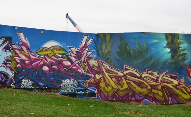 two text murals on hoardings, on the right is poser, and on the left is one with two eel heads poking up on top