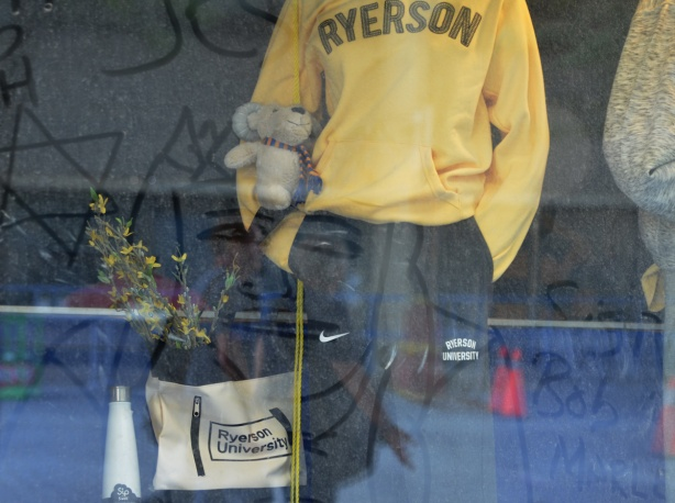 in the window of the Ryerson bookstore, mannequin wearing yellow Ryerson sweatshirt, dirty window, someone has drawn the picture of a man's face in the dirt