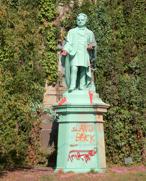statue of Egerton Ryerson at Ryerson University on Gould Street, painted green, with some red paint graffiti as well as red hands