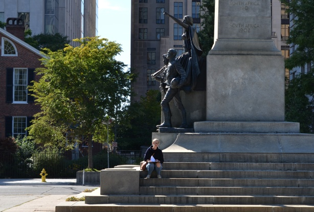 a person is sitting on the steps of the staue on University Ave