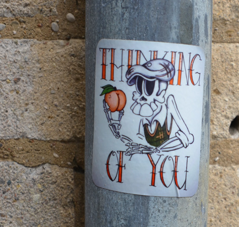 a sticker on a pole that says thinking of you, a skeleton is holding a pumpkin, also wearing a tam, big teeth on the skeleton