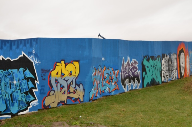 on blue hoardings, a row of text graffiti
