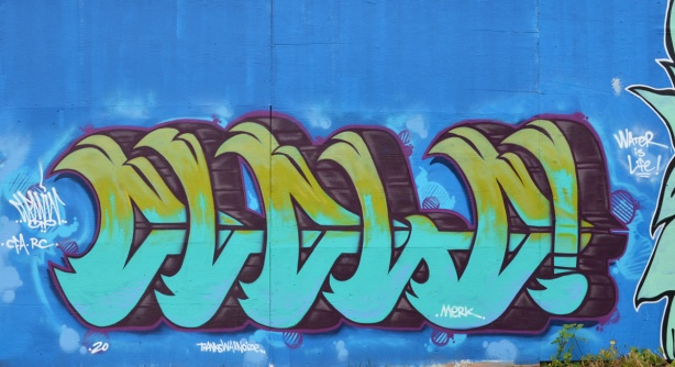 throw-up style graffiti on mural in light blue and olive green