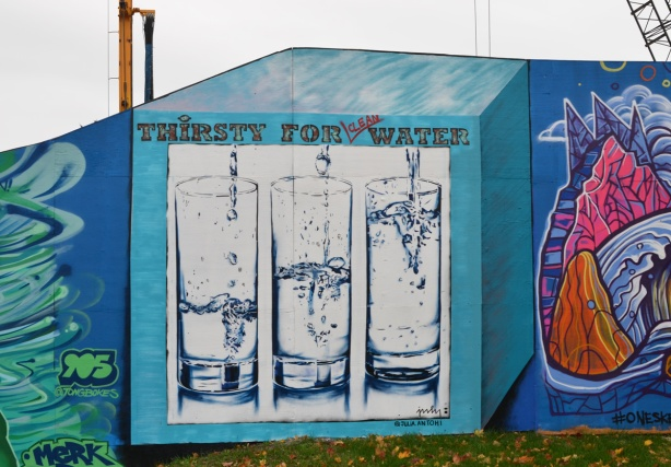 three tall glasses of water, each with a different amount, with the words thirsty for clean water, in a turquoise box, a mural