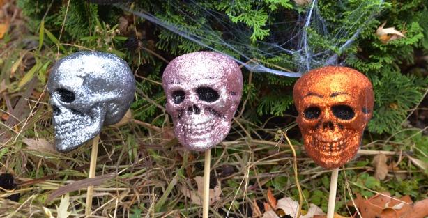 shiny glittery small skulls in a line in a garden