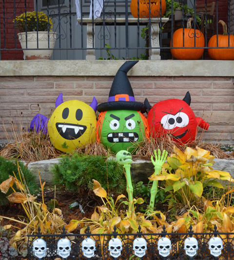 inflatible Halloween decorations in a front yard, a yellow happy face with fangs, a green witch head with a black hat, and a red devil head with pointy ears