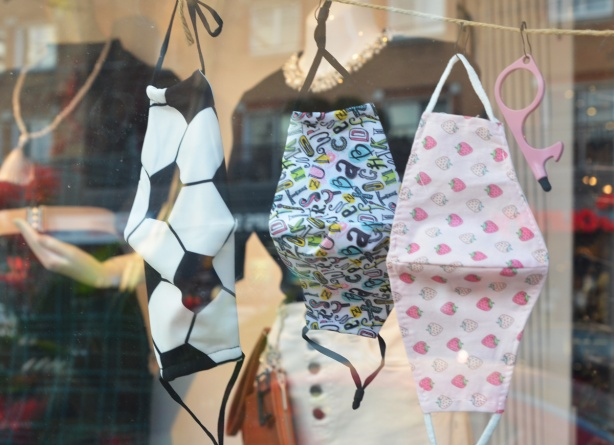 three masks on display in a store window.  One has a soccer ball pattern, another is pink with little strawberries.  The one in the middle is covered with a jumble of letters of the alphabet
