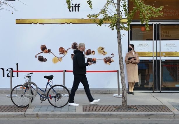 a man with earbuds on walks past the TIFF lightbox theatre where a woman in a beige long coat and a black mask is standing by the door