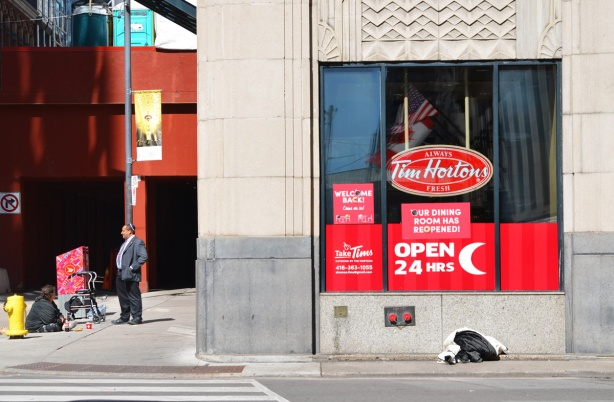 a Jewish man stands outside a TIm Hortons talking to a woman who is sitting on the sidewalk pan handling. downtown Toronto