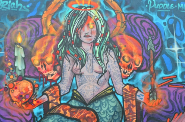 mural, long haired woman with nose ring, topless, upper body covered with tattoos, with scarves over her arms, halo on head, skulls beside her and a burning candle in each hand