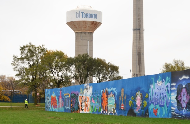 city of toronto concrete water tower behind blue hoardings with street art murals on them