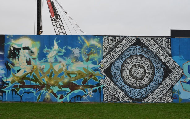 two murals on hoardsing with crane behind.