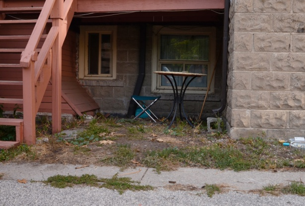 a folding chair and a small round table set up under a back porch behind a stone building, dark