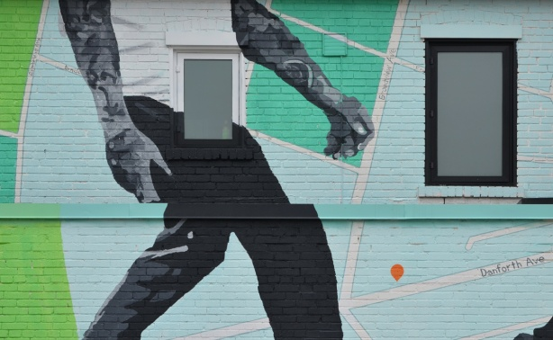 upper part of a mural on the Danforth of a man walking on a map of the area, around two windows of the building on which it is painted.