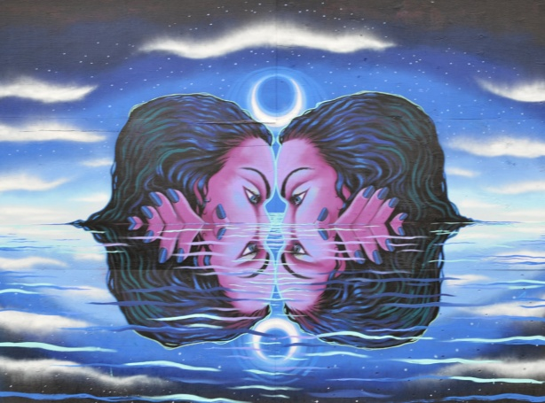 mural by Julii McMillan of two identical heads nose to nose in the water up to their noses, reflections of the two. hands beside heads so they reflect too. water, dark, moonlight
