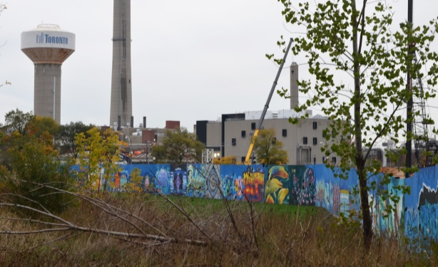 hoardings around a construction site that have been painted by wallnoize, a group of street artists who have each painted a mural on a section of the wall with city of Toronto water tower behind