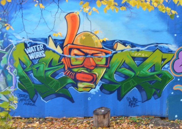 mural on hoardings near Ashbridge Bay water treatment facility, wallnoize project, head of bald man with diving mask and snorkel, in the water,
