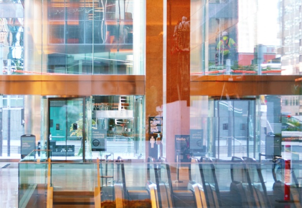 window washers and reflections, looking through a glass building from back to ftont, escalators down, high ceiling,