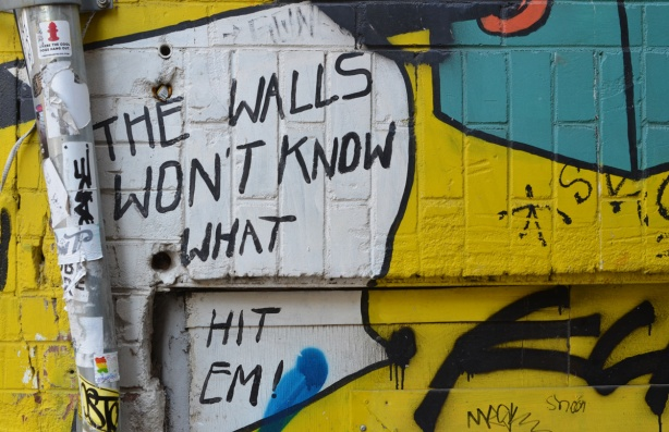 part of a mural on a wall, words that say the walls won't know what hit them.