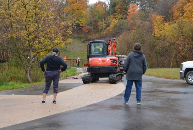 two people with their backs to the camera stand on a path and watch a digger in front of them, there is a bridge over the creek ahead and workmen have parked their truck on the bridge, autumn colours in the trees around them.
