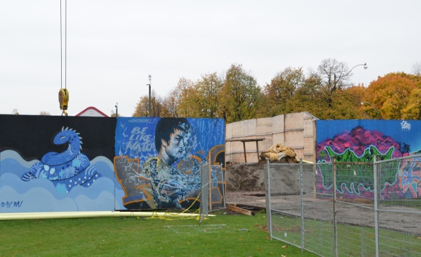 wallnoize street art murals on blue hoardings around new water treatment plant, by an entrance to the site, a mural of a man