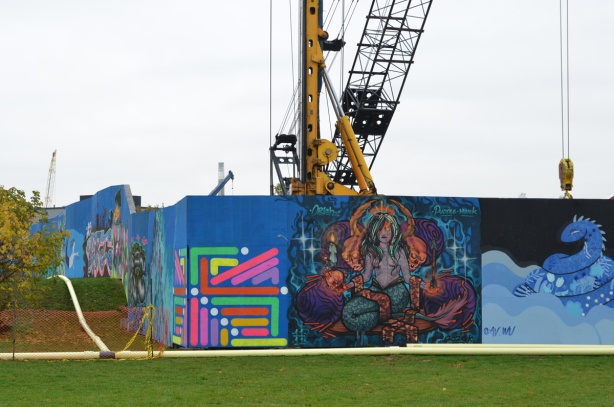 wallnoize street art murals on blue hoardings around new water treatment plant, cranes behind the fence, murals at the corner