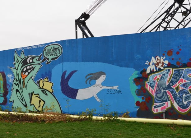 wallnoize street art murals on blue hoardings around new water treatment plant, a kizmet raccoon and a person swimming