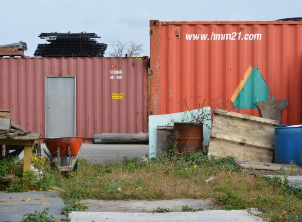 two shipping containers and some other junk used in a lot with a garden
