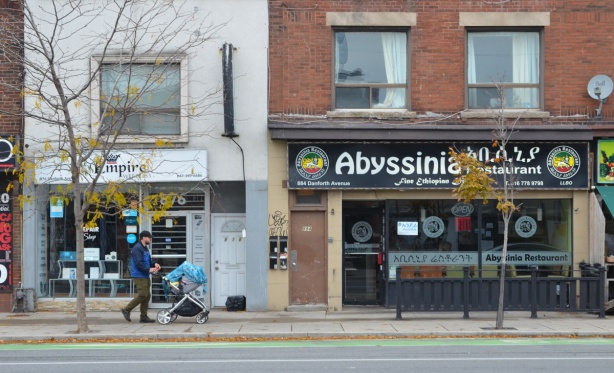 a man pushes a stroller along the sidewalk past a store and the Abyssinia restaurant on the Danforth