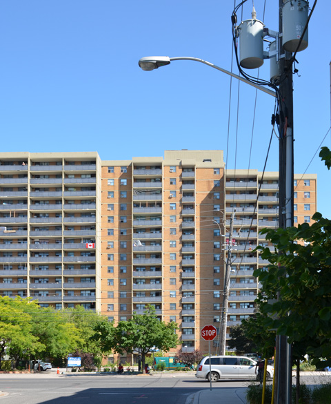 looking north on a side street towards Danforth, large multi storey apatment building