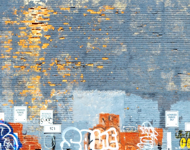 bluish grey paint on an exterior wall that is peeling to reveal the bricks below, tags and graffiti along the bottom part of the wall, parking signs too