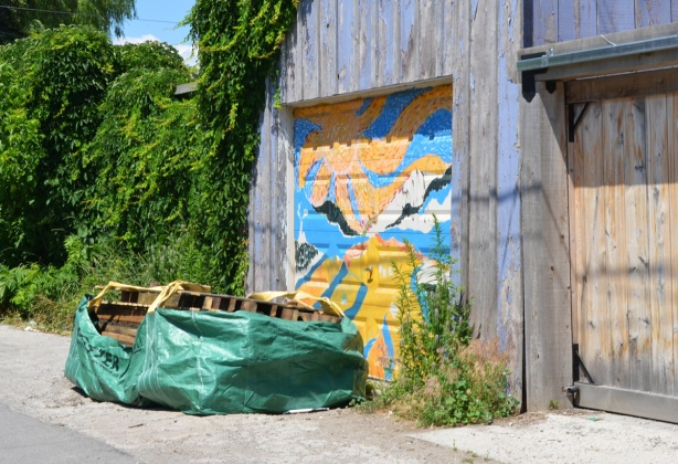large green plastic bag on the ground filled with wood palletts, in an alley, in front of a garage door with street art on it