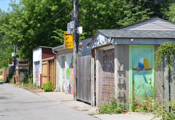 garages in an alley with garage doors that have been painted with street art, the garage in front has a light greens side door with two birds sitting on a braanch painted on it