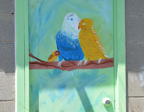 street art painting of two birds sitting on a branch, a yellow bird and a blue bird with a white head.