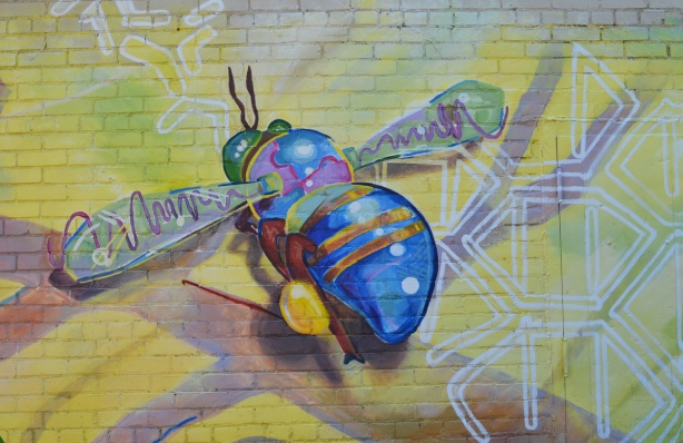 bee with blue body and bum in a mural