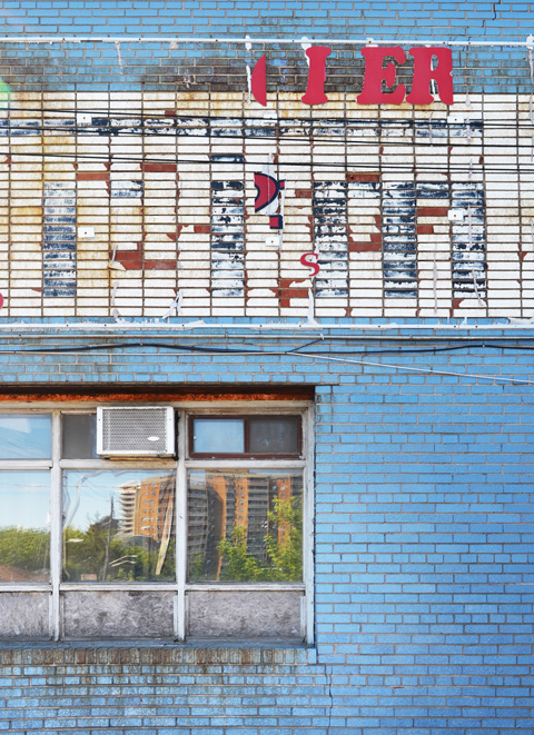 brick wall painted blue with a large window, air conditioner in the window, lower panes covered with grey plywood, reflections in the window, old sign above the window that is fading and paint peeling